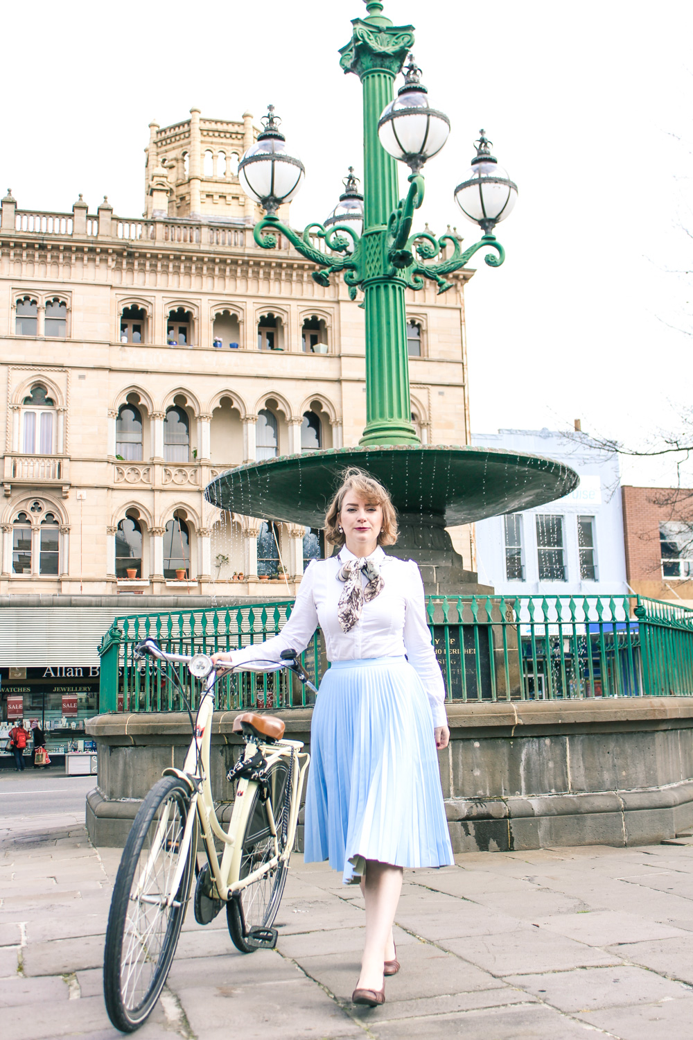 @findingfemme wears pleated leather blue skirt and rides a vintage bike in Ballarat