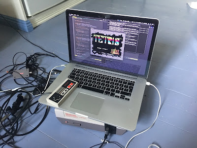 [Image: A powered-on NES console and a MacBook on top of it, showing a Tetris title screen.]