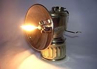 Parabolik bir yansıtıcı ayna içinde yanan aleviyle aydınlatan bir karpit lambası