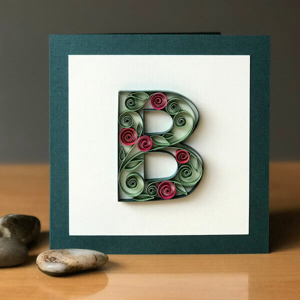 Quilled uppercase letter B filled with quilled flowers on card front