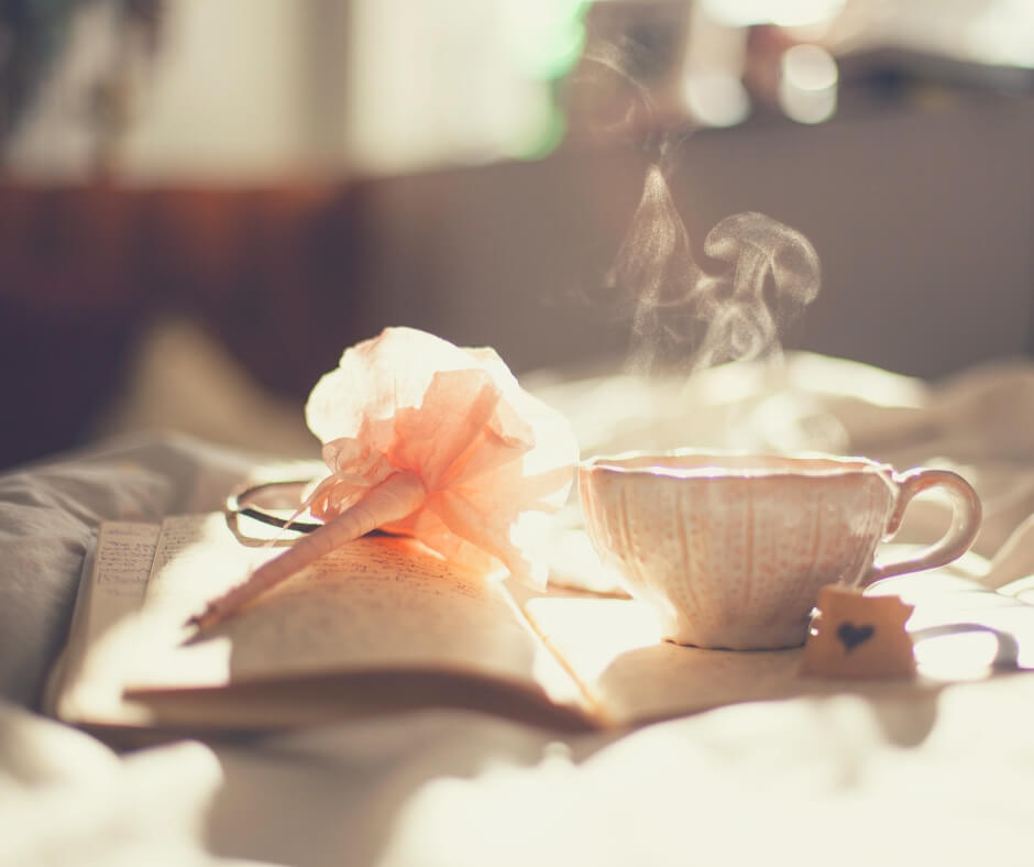 A pen, a notebook, and a steaming cup of tea, sit on a bed with rumpled covers.