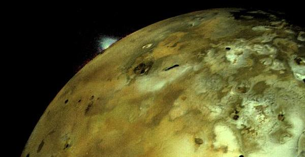 Voyager 1 acquired this image of Io on 4 March 1979 at 5:30 p.m. (PST) about 11 hours before closest approach to the Jupiter moon. The distance to Io was about 490,000 km (304,000 miles). An enormous volcanic eruption can be seen silhouetted against dark space over Io's bright limb. The brightness of the plume has been increased by the computer as it is normally extremely faint, whereas the relative color of the plume (greenish white) has been preserved. Credit: NASA