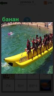 В море желтый банан, на котором сидят люди и катаются на нем