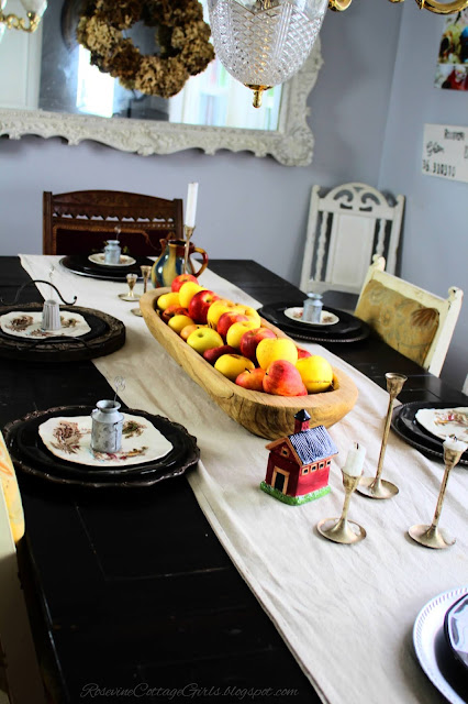 black table with beige table runner with wooden dough bowl on top filled with red and yellow apples Table set for a meal.  rosevinecottagegirls.com apple tablescape, farmhouse table decorFall Decor, Autumn Decorating, Table Decor, Cottage, Country, Natural Decor,