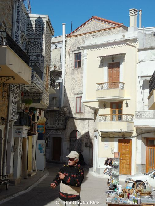 uliczka wioski Pyrgi w tle dom Krzysztofa Kolumba, na pierwszym planie mężczyzna w czapce z daszkiem