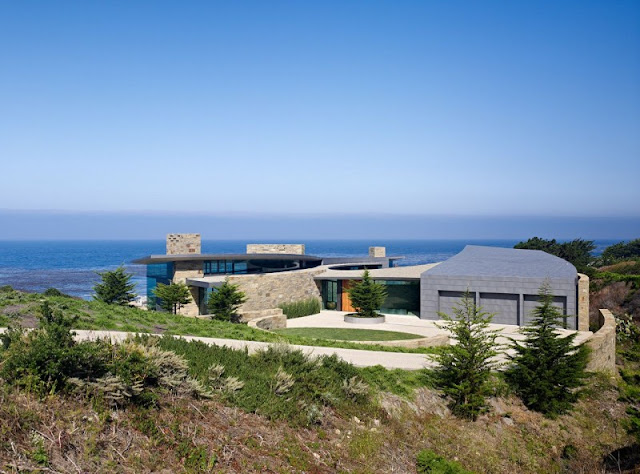 Picture of the modern house as seen from the land with the ocean on the background