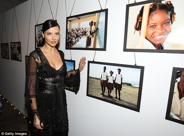 Adriana posed in front of professional Haiti artwork at the fundraiser