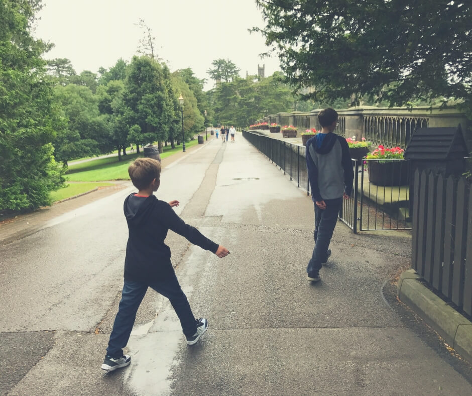 Two young boys walk along a path wearing jeans, jumper, and trainers.