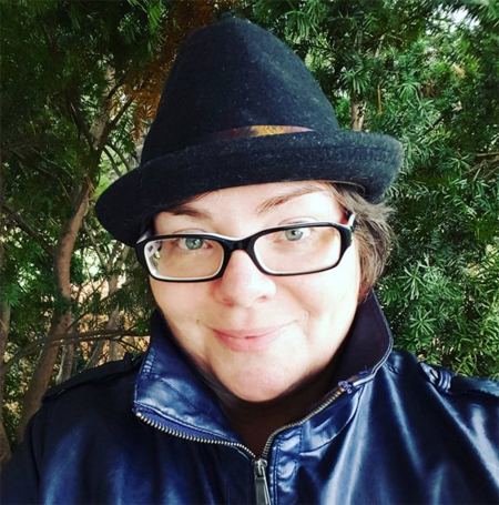 image of me outside wearing a blue moto jacket, black-and-white framed glasses, and black fedora hat