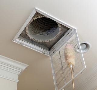 A person dusting an air vent