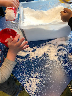 kids playing with artificial snow on table