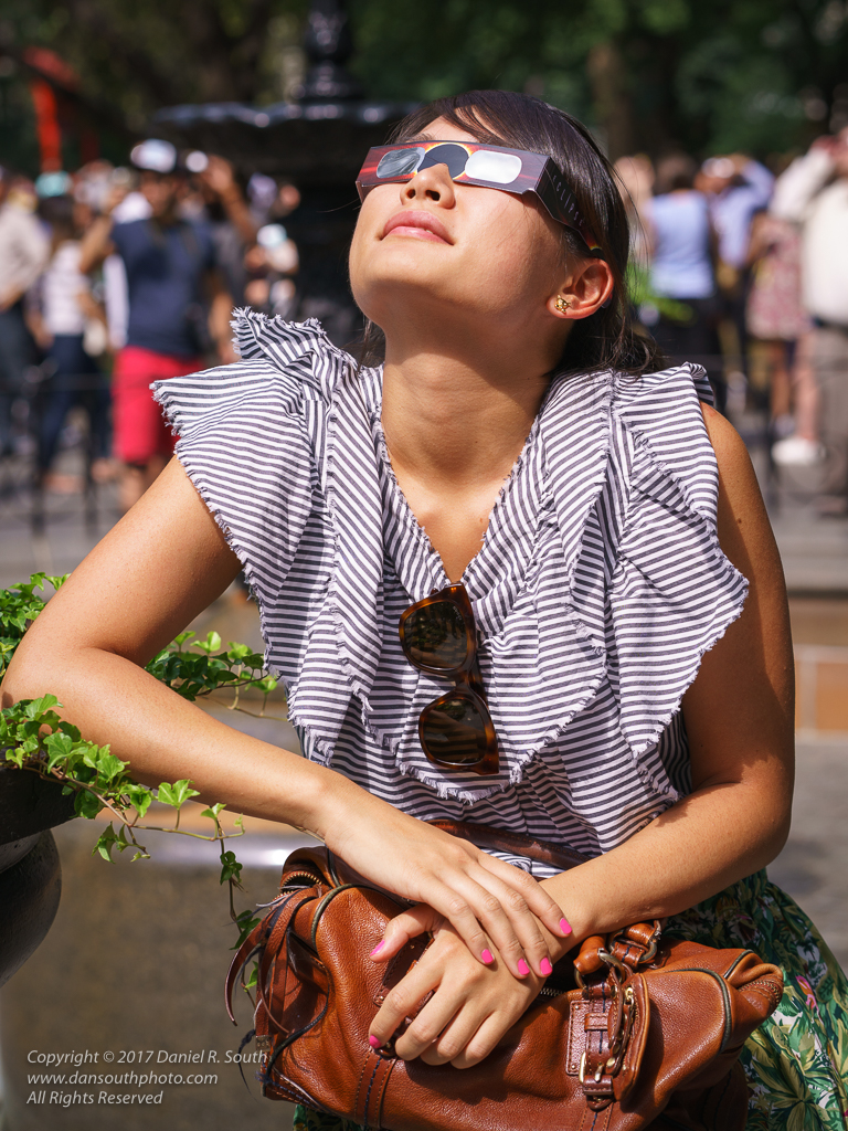a photo of a young woman wearing protective glasses for viewing the eclipse
