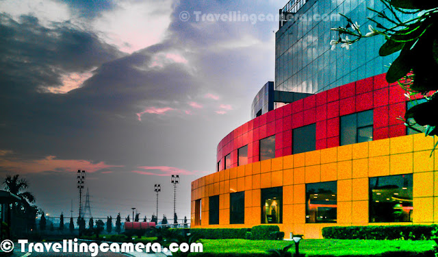 Adobe India has one of the most colorful building in Noida city near to Capital city of India. This Photo Journey shares some of the mobile clicks of Adobe Noida campus from outside. Let's check out and know more about the same.Adobe Noida building with these vibrant colors was first building in sector 25A of noida. Till date, there are only two buildings in the city center sector of Noida. After one of the biggest real estate deals in Noida, Wave group has acquired rest of the sector now and building various facilities around the same. Here is a photograph of beautiful landscapes in the campus - Water fountains, green plants, colorful tiled platforms etcWhole building remains clean most of the times because of continuous cleaning efforts in campus. This building is also one of the rare green buildings in the city. Adobe Noida building has been awarded various recognitions for green efforts in the city. Adobe office in Noida is just in front of Sport-Stadium in sector 21A and Reliance building in sector 24. It's on the corner of sector 25A, facing Sector 24 on one side and sector 21A on the other side.Campus has small golf ground, half basketball court, Volleyball court & lawn tennis facilities apart from various recreational options inside the building.