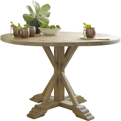 French farmhouse style round table in a grey white-wash with green plants displayed.