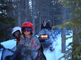 Snowmobile tour with five guests, riding on a trail through the trees.