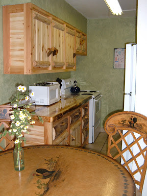 Kitchen with beautiful log cabinets, tile floors, and faux green walls.  Dinning table with faux painting of a rooster with 2 chairs.  Fresh wild flowers in a bottle on the table.