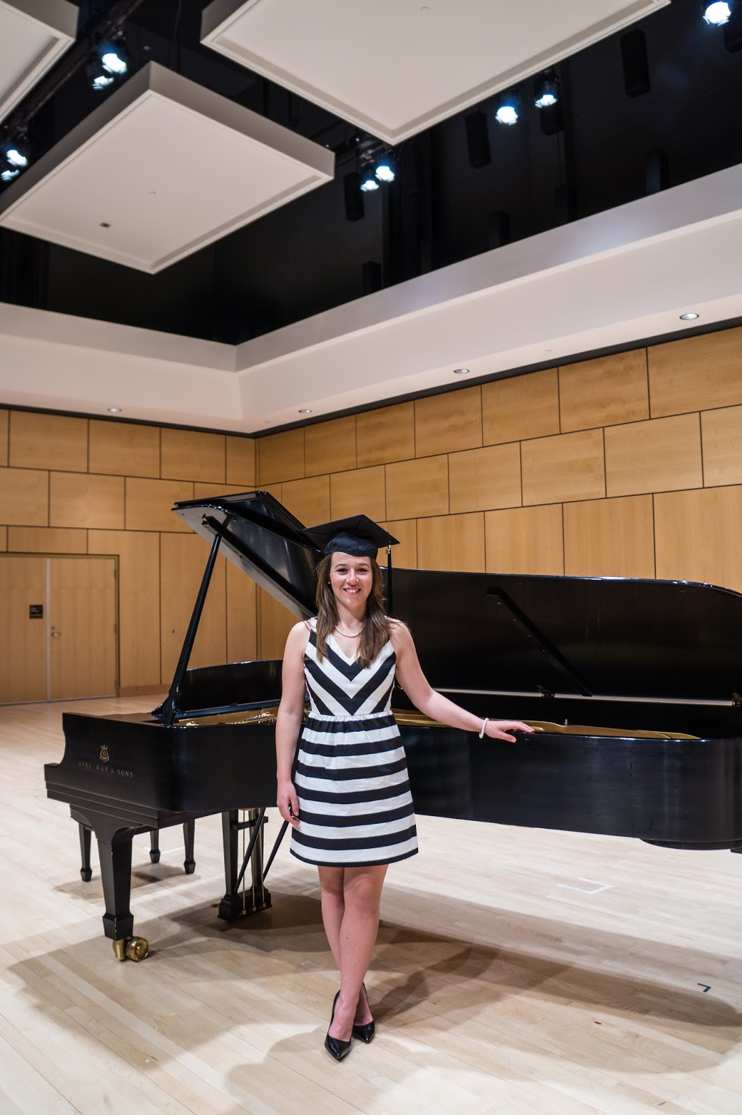 Graduate in her cap standing in front of a piano in a blonde concert hall.