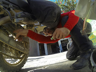 Pedro lubrificando a corrente de sua moto.