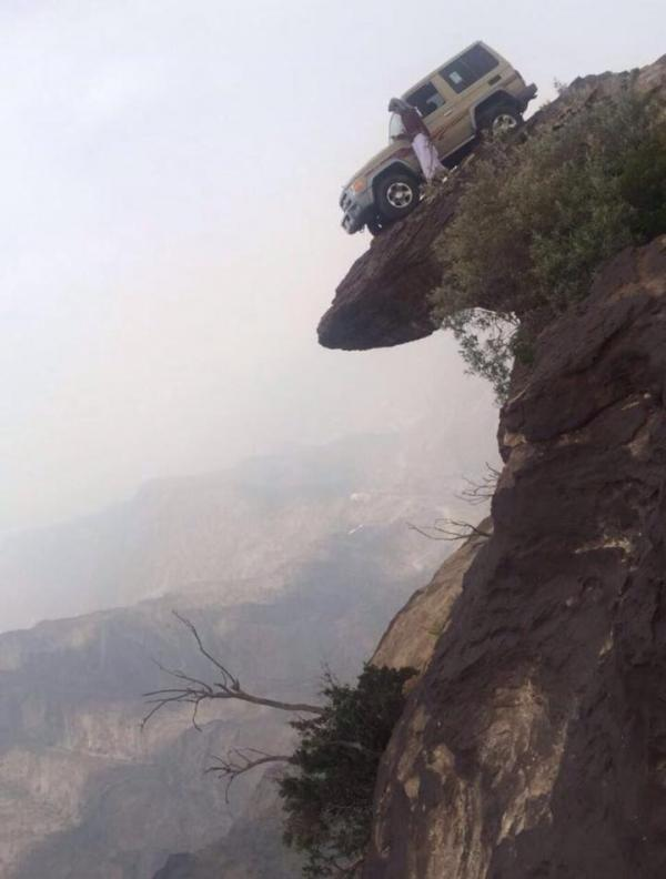 An Arab daredevil drove his car to the edge of a cliff of the Fifa mountain in Saudi Arabia.   A photo probably taken by a companion shows the traditionally dressed man standing next to his car inclined at about 60 degrees.  He seems to have pulled out his camera to get a good view of the scenery from 3,500 metre above sea level.