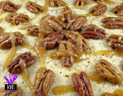 extra maple covered pecans on top of a creamy and delicious cheesecake
