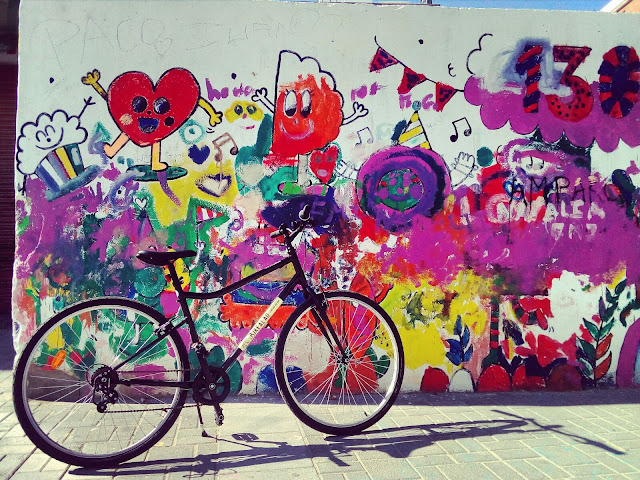 BikeAlao trekking bike in front of colourful street art in Cabañal