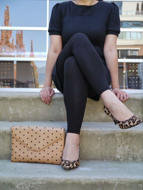Little black sweater dress worn with black leggings, leopard print pumps, pearl stud earrings, red lipstick, and a black-and-tan polka dot clutch.