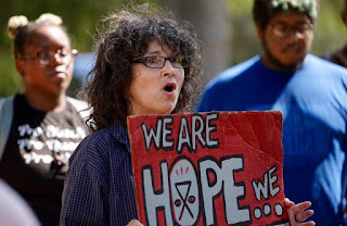 Woman hold sign that says We are HOPE