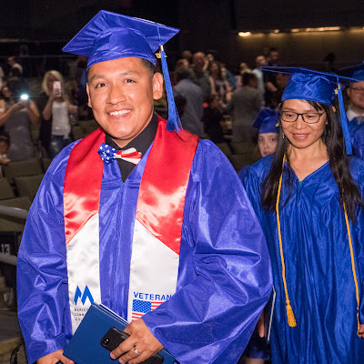 Image of a male grad smiling at camera, wearing Maricopa Veterans regalia.
