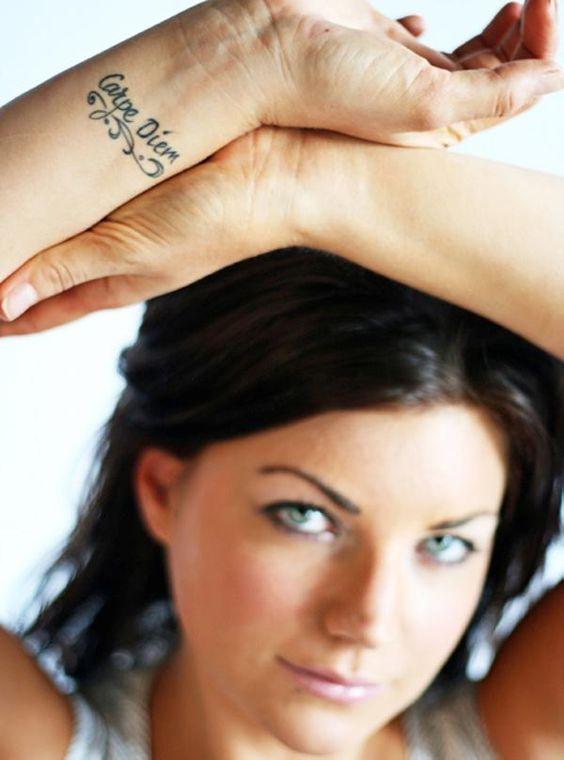 Foto de mujer, lleva tatuaje de carpe diem en letras cursivas,el tatuaje esta en su muñeca derecha