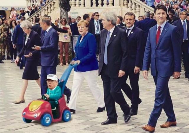 Merkel pushing Trump in a baby stroller
