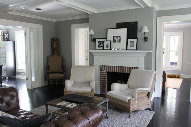 Modern farmhouse decor in living room with fireplace and leather Chesterfield sofa on Hello Lovely Studio