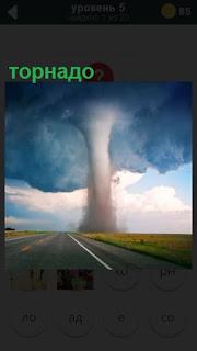 торнадо поднимается к небу, впереди пустая дорога