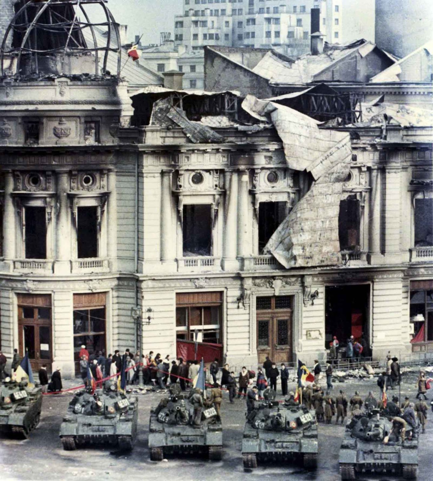 Civilians standing behind tanks after a battle between the army backed up by armed civilians and pro-Ceausescu supporters in Bucharest.