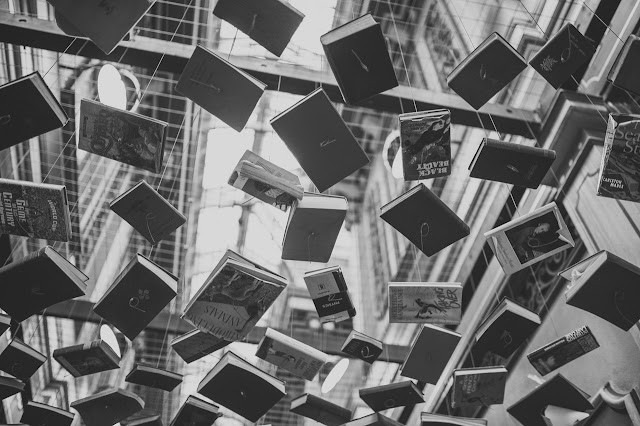 Floating books in the air, black and white, tied to strings