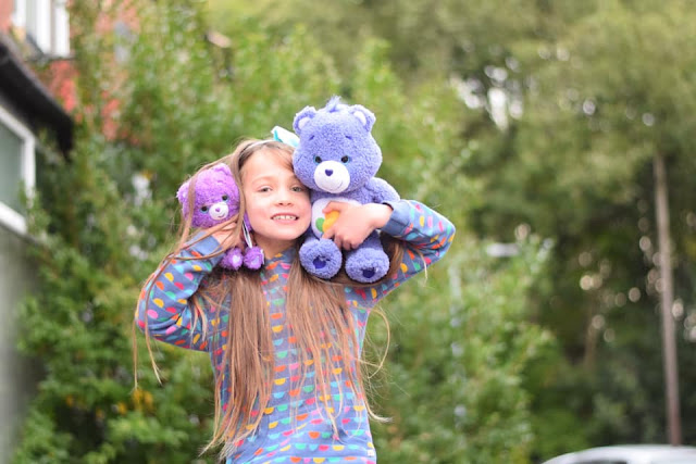 child holding care bear harmony bear and share bear