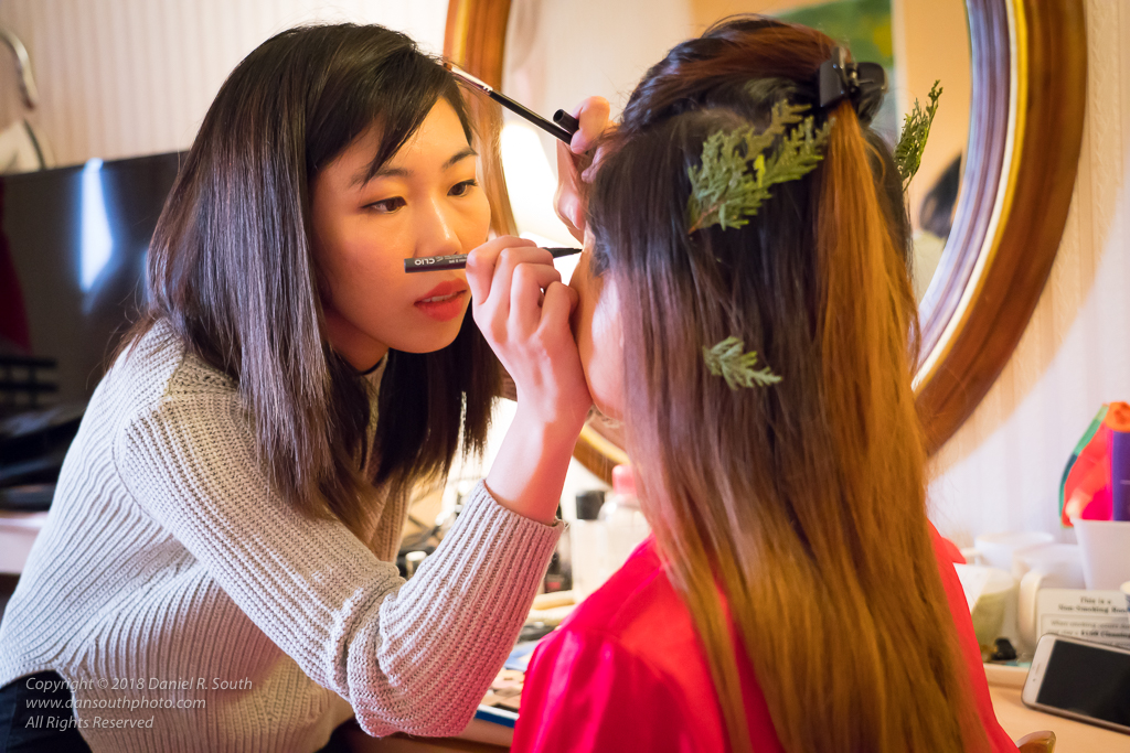 a photo of a makeup artist preparing a bride for a wedding