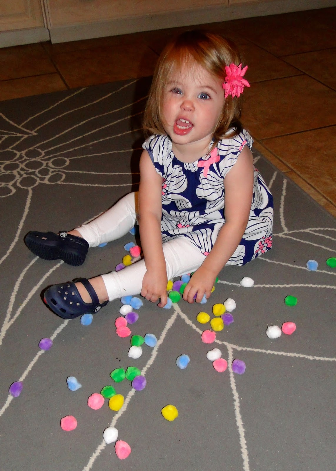 toddler girl playing with Pom Poms