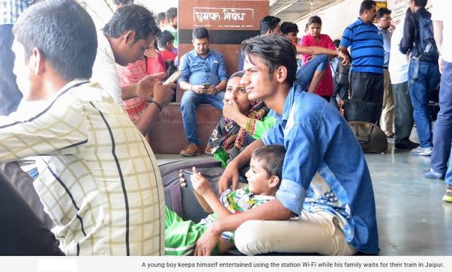 Seorang anak laki-laki Yang Dirinya terhibur mengakses internet dengan menggunakan WiFi Stasiun, bersama keluarganya sambil menunggu kereta api yang akan membawa mereka di Stasiun Jaipur.