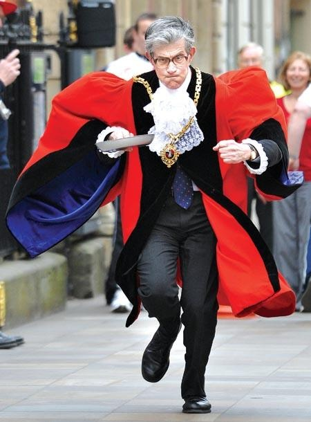 The Mayor of Worcester participates in The Worcester Rotary club annual pancake race. Councillor David Tibbutt races in traditional robes while holding a pancake in a skillet. Court Complexities and Legal Fiction, A Moron In A Hurry marchmatron.com