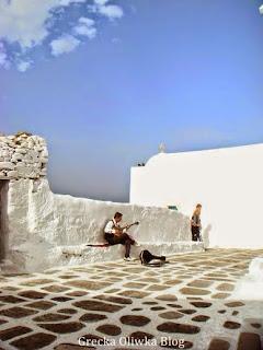 Mężczyzna siedzi na ławce na jednej z uliczek Mykonos i gra na buzuki
