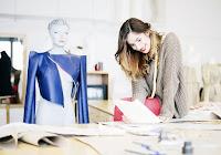 Bir modacı dükkanı ve bir model üzerinde dikilmekte olan bir bayan montu tasarımı