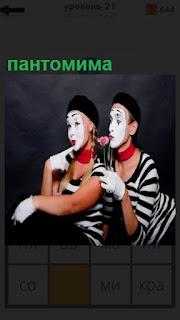двое людей изображают пантомиму с масками на лицах