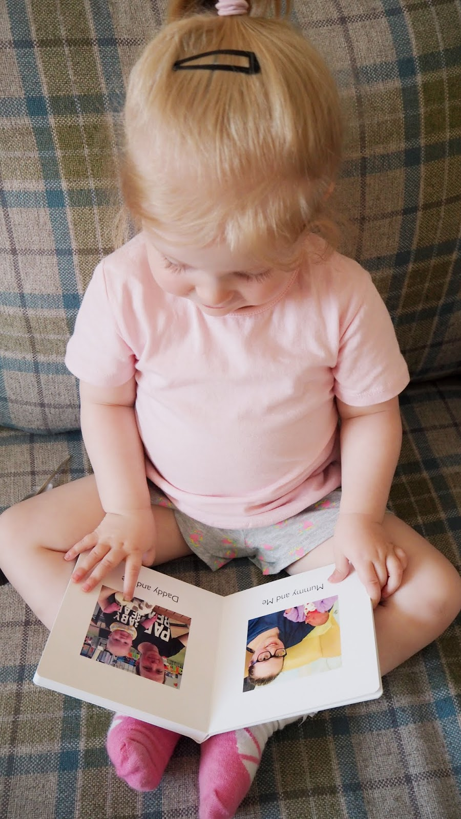 Elise looking down at her photo book and pointing to a picture of her and her daddy