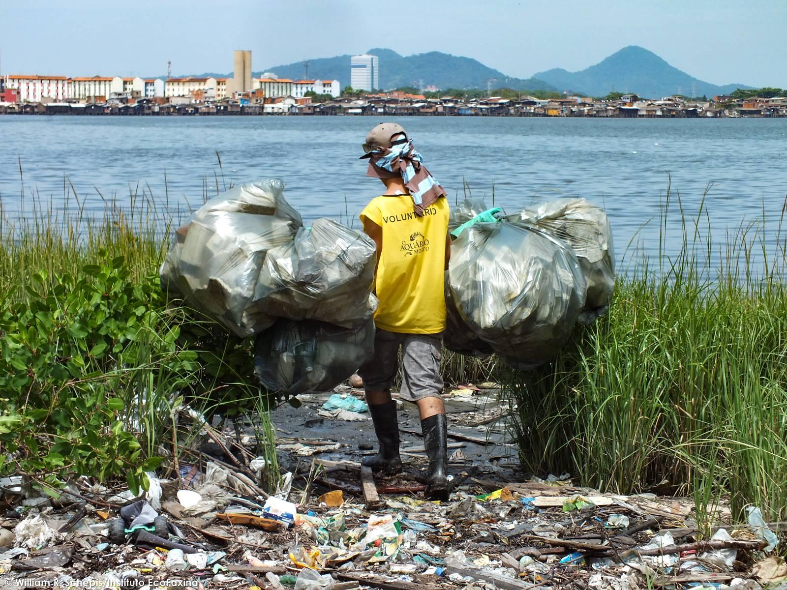 Voluntário carrega sacos com isopor e plástico. Ao fundo, uma favela de palafitas.