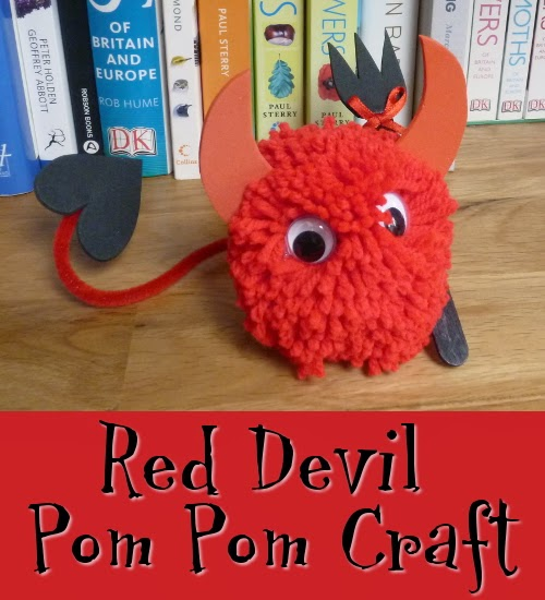 Red wool or yarn pom pom decorated to look like a devil character