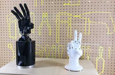 Pic of one black and one white robotic hand in exhibition with tool outlines on backdrop