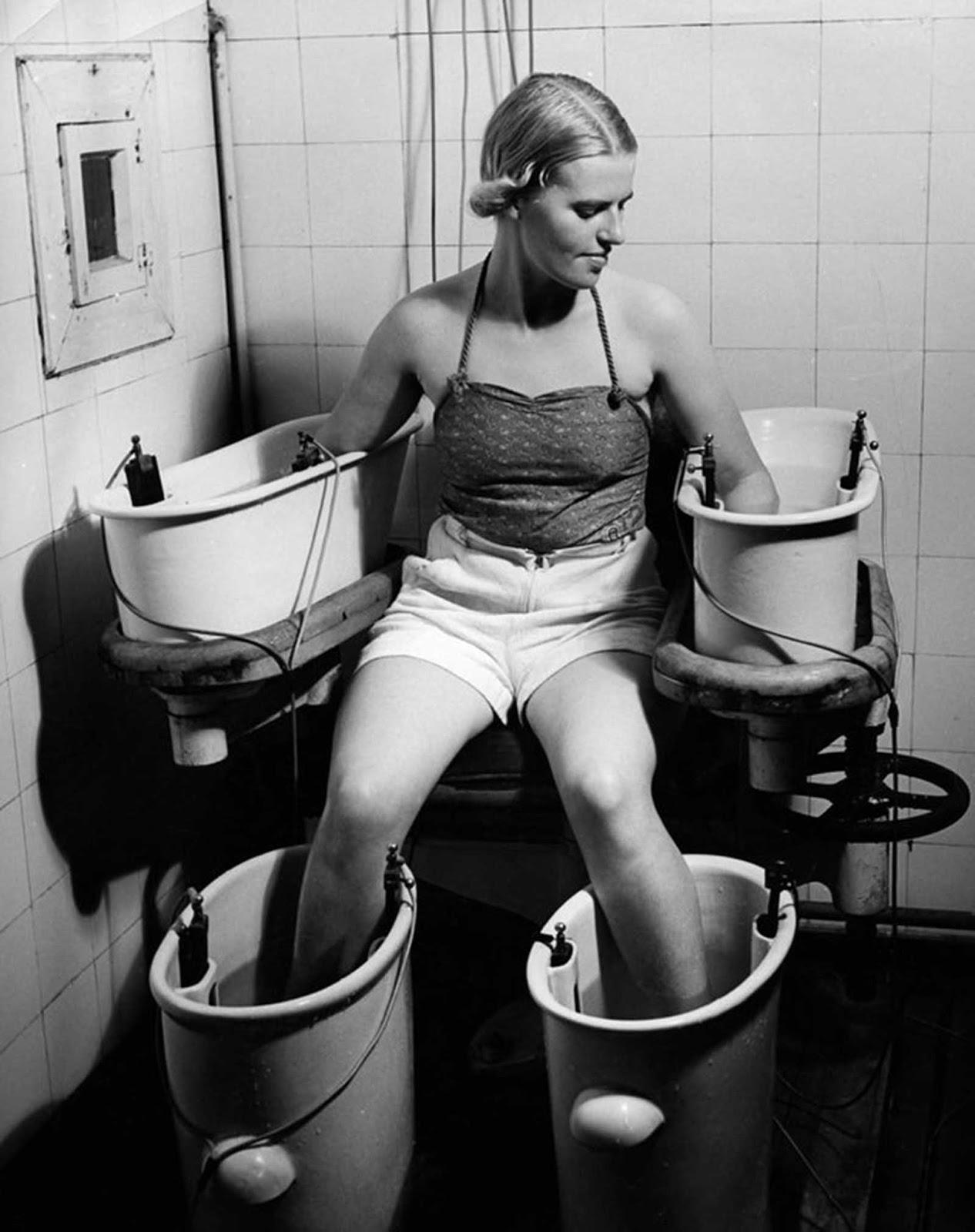 Una joven sostiene sus brazos y piernas en cuatro baños de agua con corriente eléctrica, para mejorar la circulación sanguínea, alrededor de 1938.