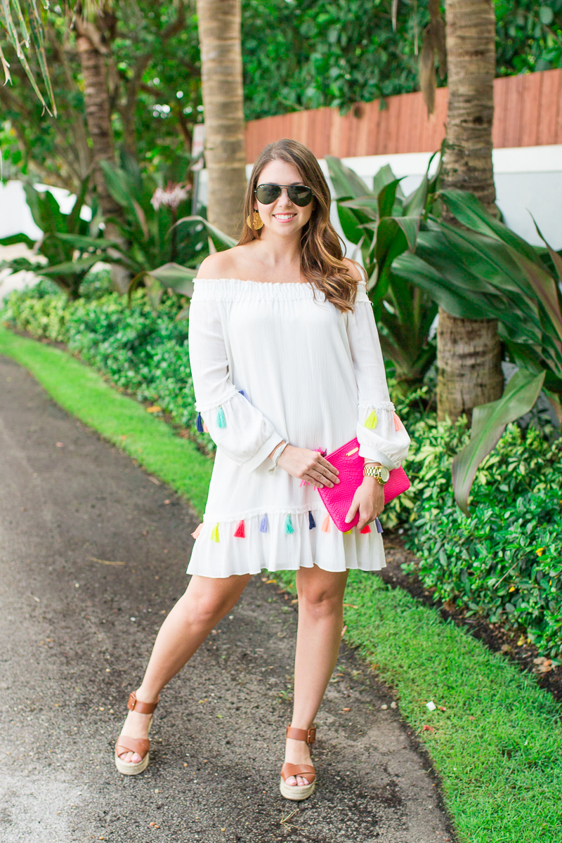 Colorful tassels add detail to this white off the shoulder dress.