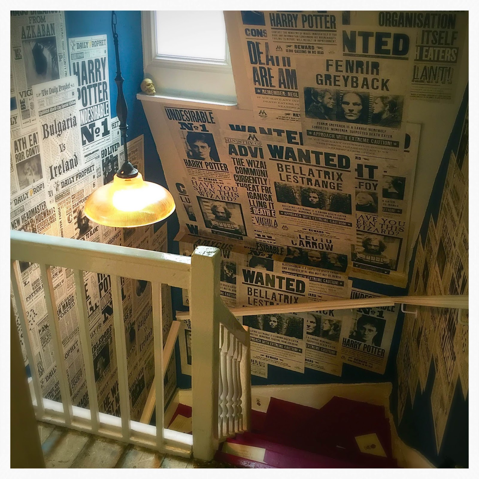 staircase at the house of minalima plastered in The Daily prophet from the Harry Potter movies
