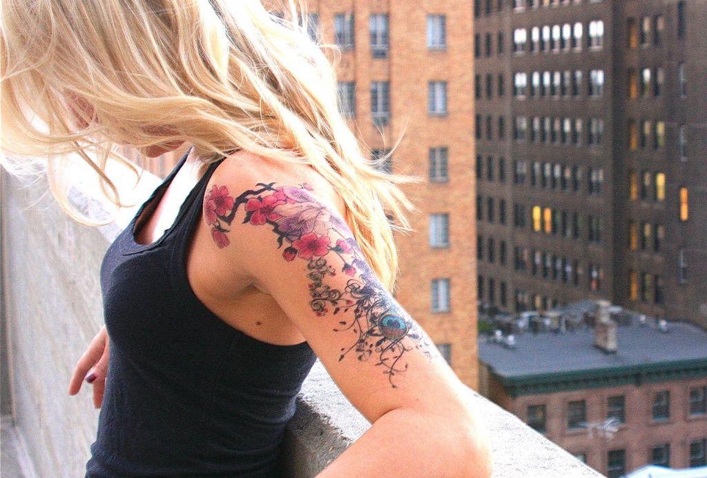 Chica rubia en la azotea de un edificio de New York, apoyada en la cornisa vemos su tatuaje de flores en un brazo